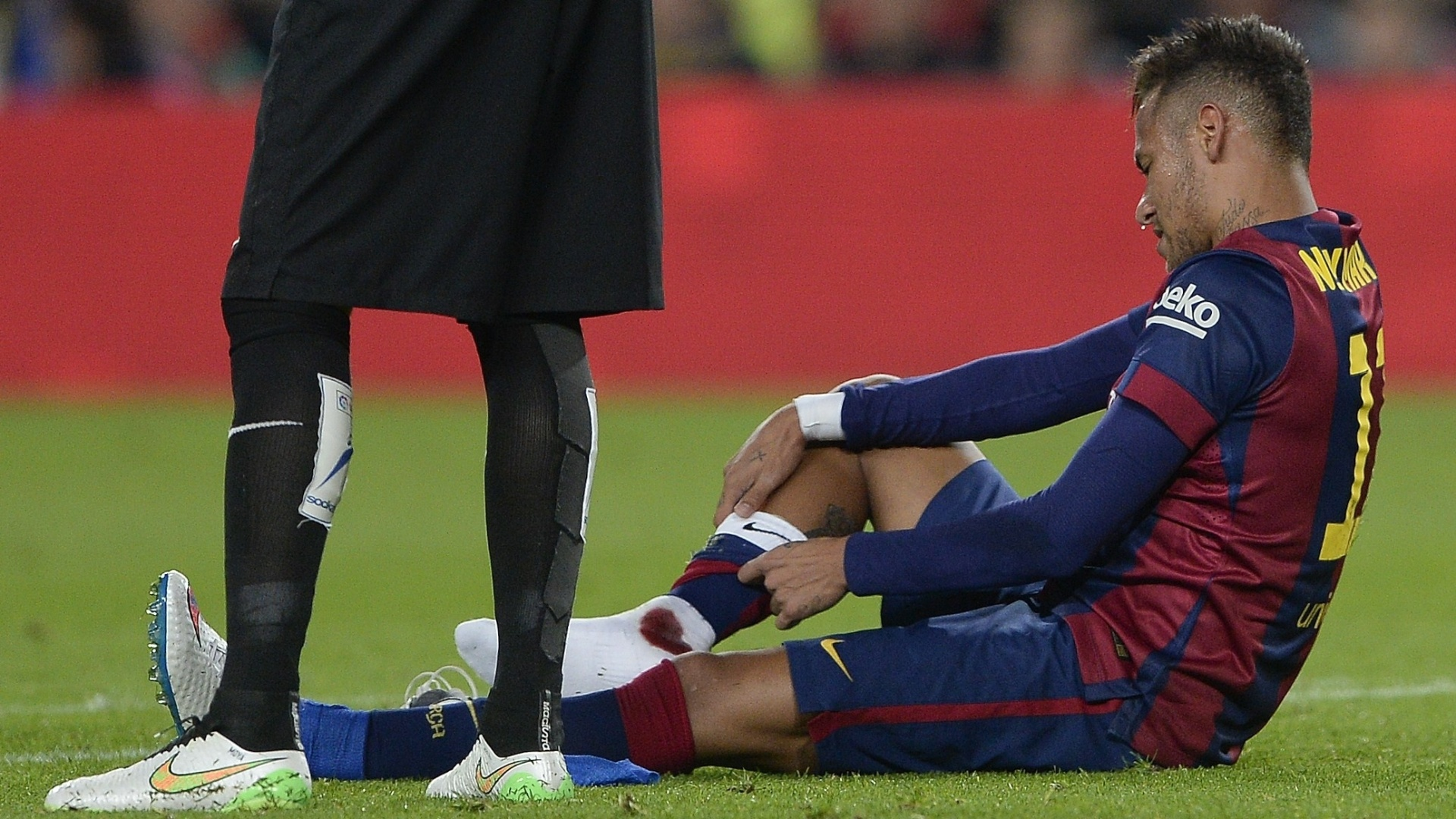 Neymar se machuca e precisa trocar o meião, ensanguentado, durante o 1ª tempo do jogo entre Barcelona e Atlético de Madri