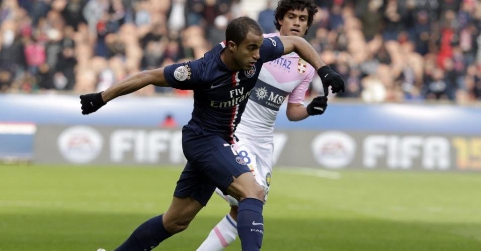 18.jan.2015 - Lucas, do Paris Saint-Germain, tenta escapar da marcação de jogador do Evian, durante partida deste domingo (18), pelo Campeonato Francês