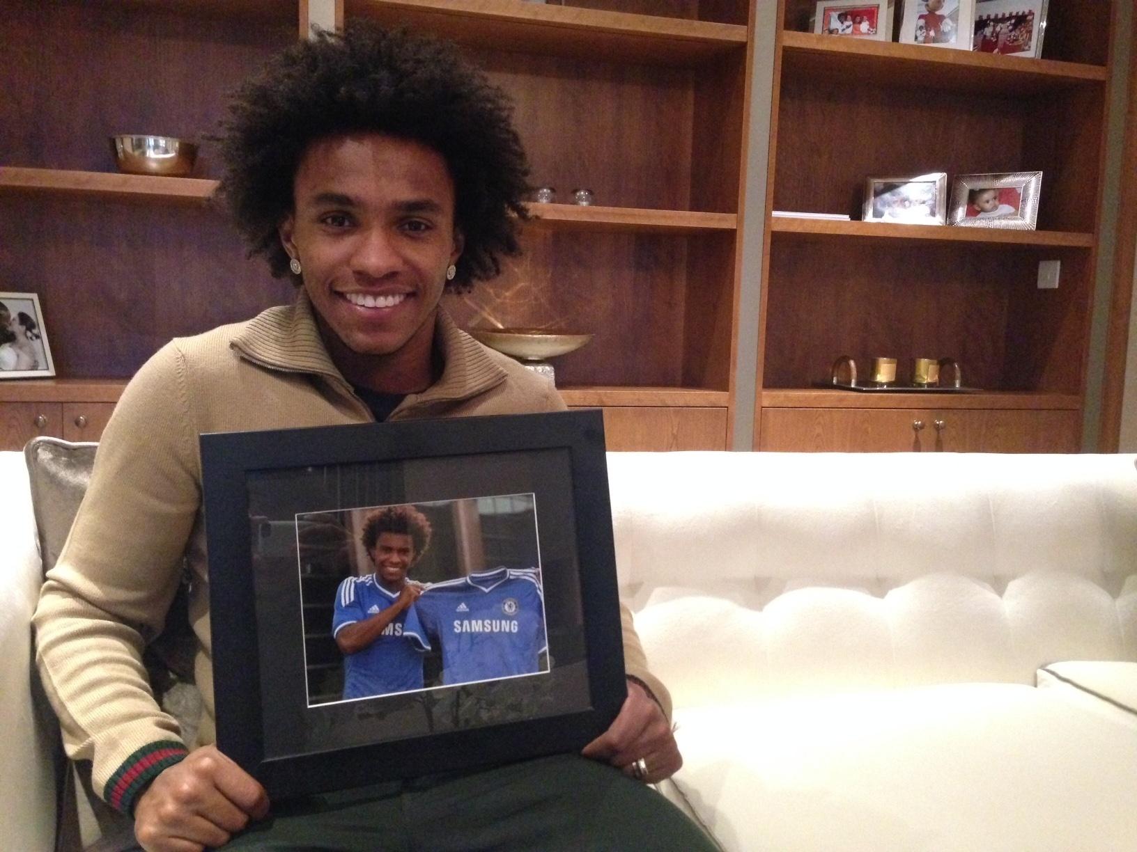 27.jan.2015 - Willian, meio-campista do Chelsea, posa na casa em que vive em Londres e comemora bom momento no clube
