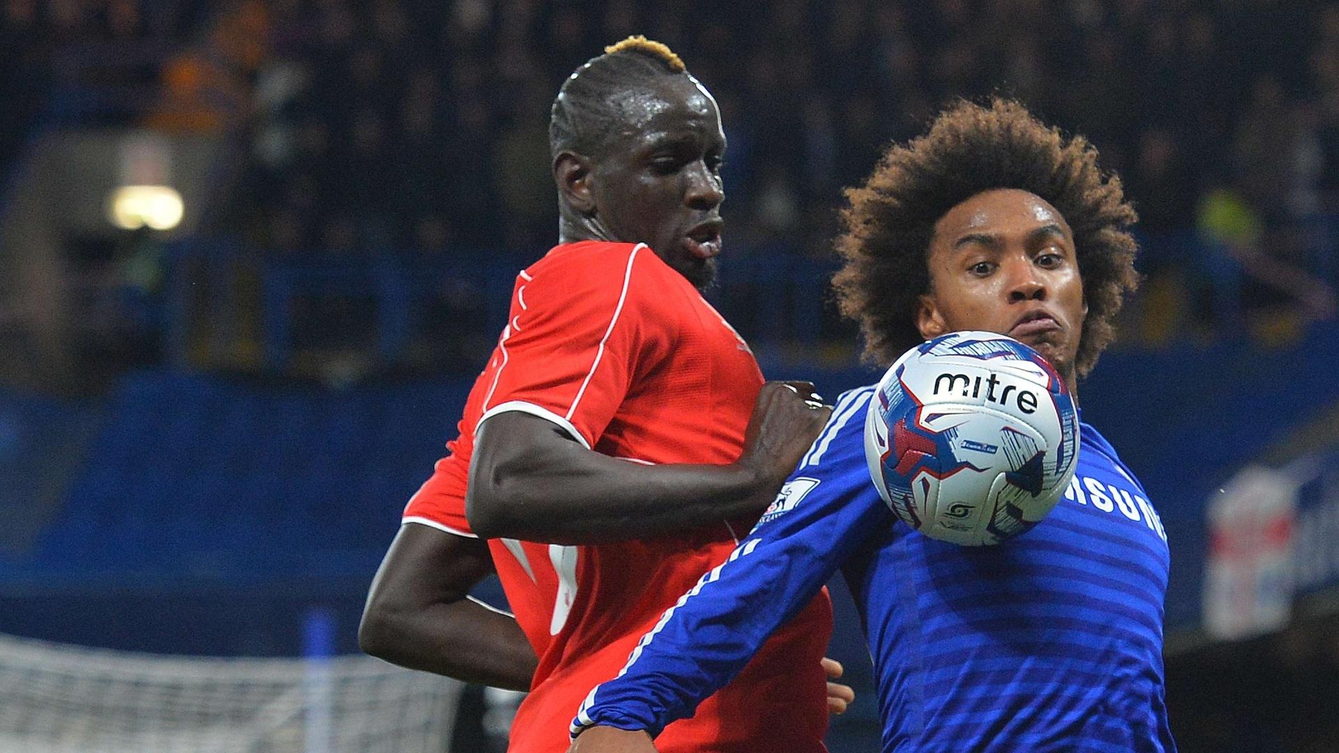 Willian, do Chelsea, domina a bola no peito e é marcado por Sakho, do Liverpool