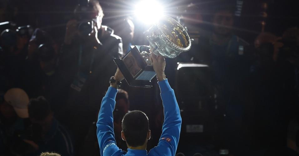 Djokovic exibe a taça para os fotógrafos na Rod Laver Arena
