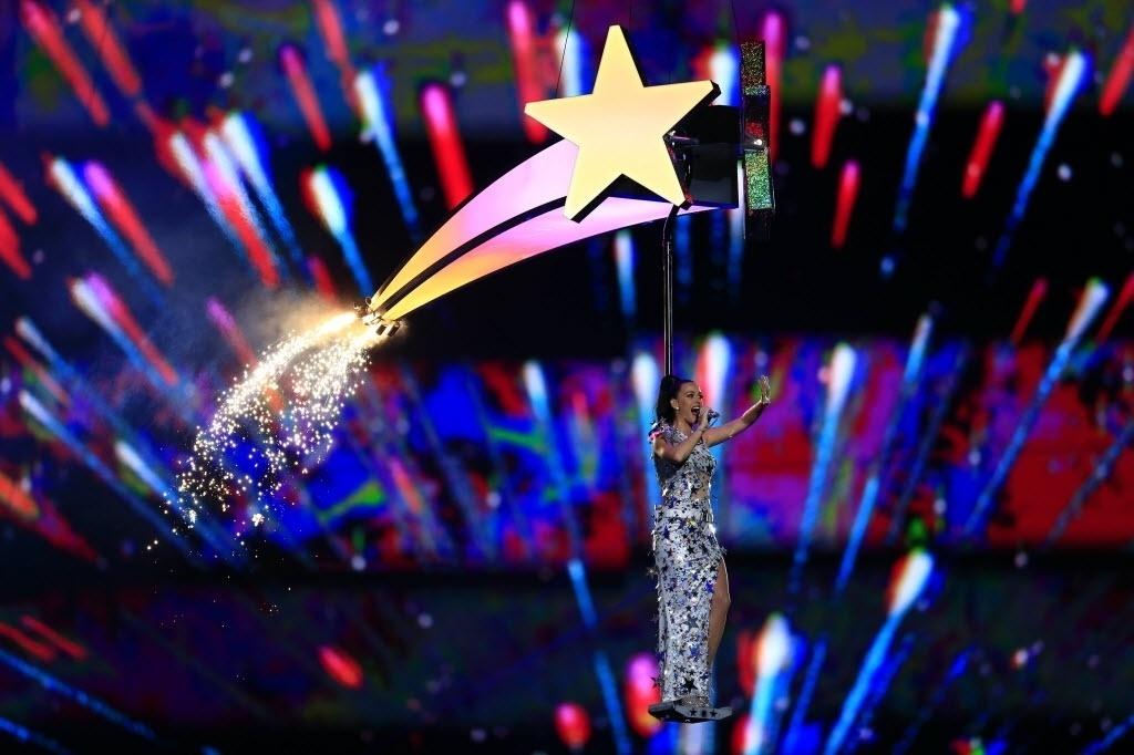 Com fogos de artifício ao fundo, Katy Perry sobrevoa o estádio de Glendale, no Arizona, cantando Firework no show do intervalo do Super Bowl 49