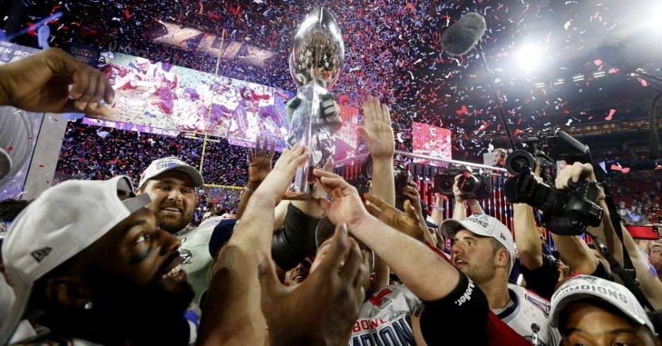 Jogadores do New England Patriots erguem o troféu do Super Bowl 49 e comemoram a vitória sobre o Seattle Seahwaks