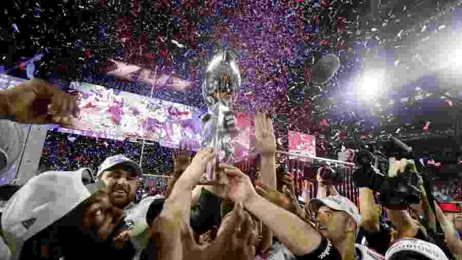 Jogadores do New England Patriots erguem o troféu do Super Bowl, prêmio máximo do Super Bowl - Christian Petersen/Getty Images/AFP