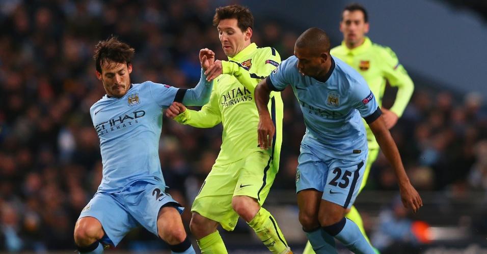 Fernandinho (à direita) e David Silva, do Manchester City, tentam tomar a bola de Lionel Messi, do Barcelona, em jogo dos dois times pela Liga dos Campeões