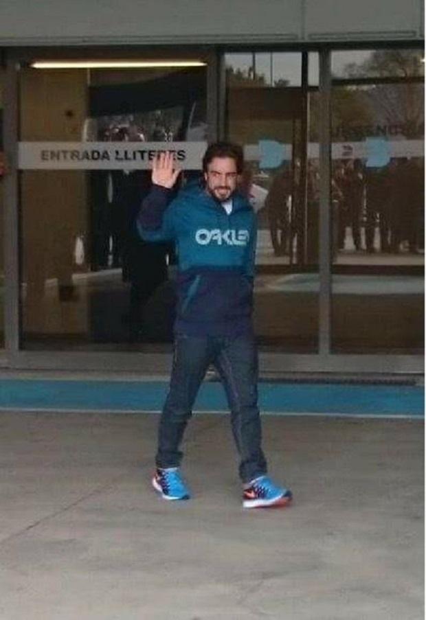 Fernando Alonso acena ao deixar o hospital em Barcelona