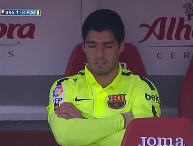 Uruguaio Luis Suárez fica cabisbaixo no banco de reservas após fazer um gol e ser substituído em vitória do Barcelona contra o Granada no Campeonato Espanhol