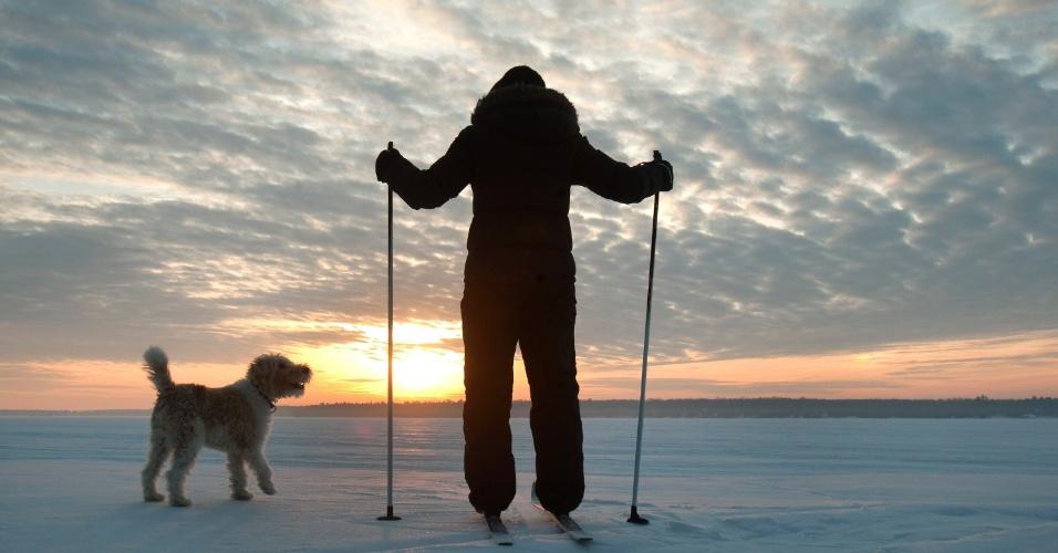 10.mar.2015 - Praticante de esqui cross-country observa o nascer do sol ao lado de um cachorro, em um lago coberto de neve na região de Kawartha Lakes, em Ontário, no Canadá
