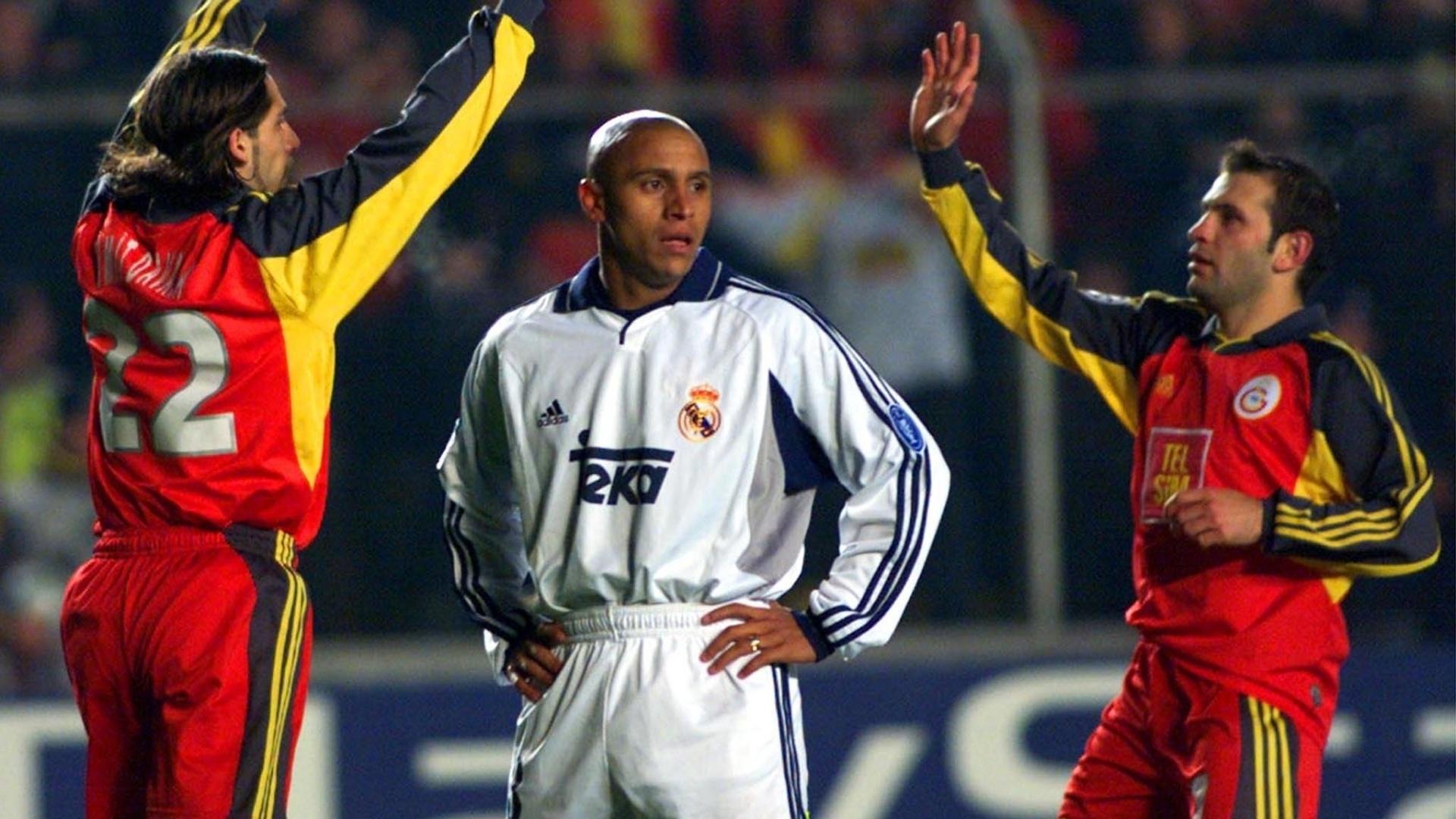 Roberto Carlos, lateral do Real Madrid, lamenta enquanto Davala e Buruk comemoram um gol do Galatasaray pela LIga dos Campeões 2000/01