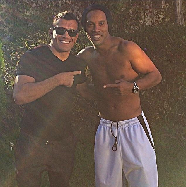 17.mar.2015 Ronaldinho Gaúcho com lutador de jiu jitsu Cobrinha no condomínio