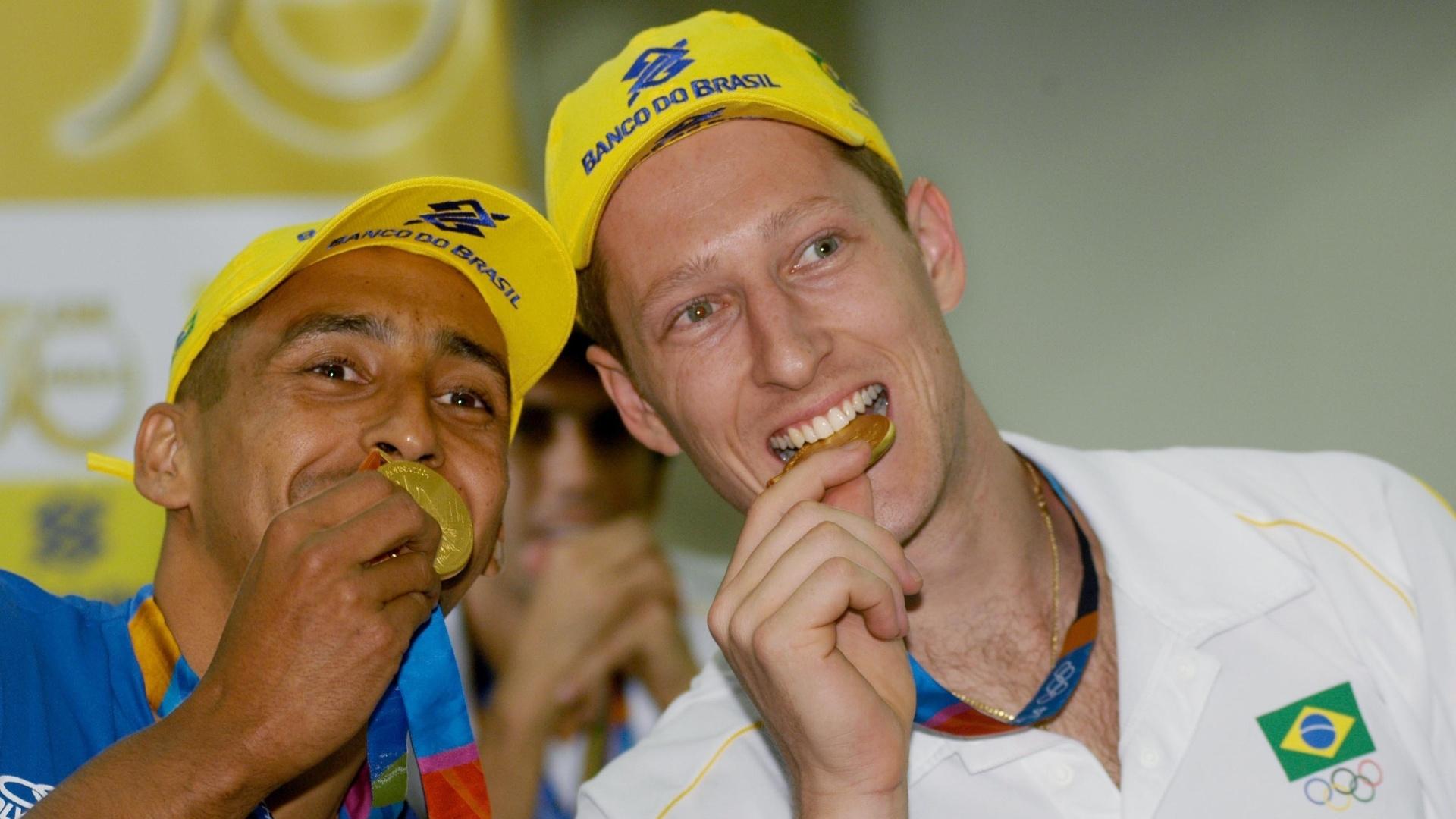 Gustavo (direita) e Serginho posam com a medalha de ouro conquistada nos Jogos Olímpicos de Atenas. Além desse ouro, Gustavo tem também a prata de Pequim-2008.