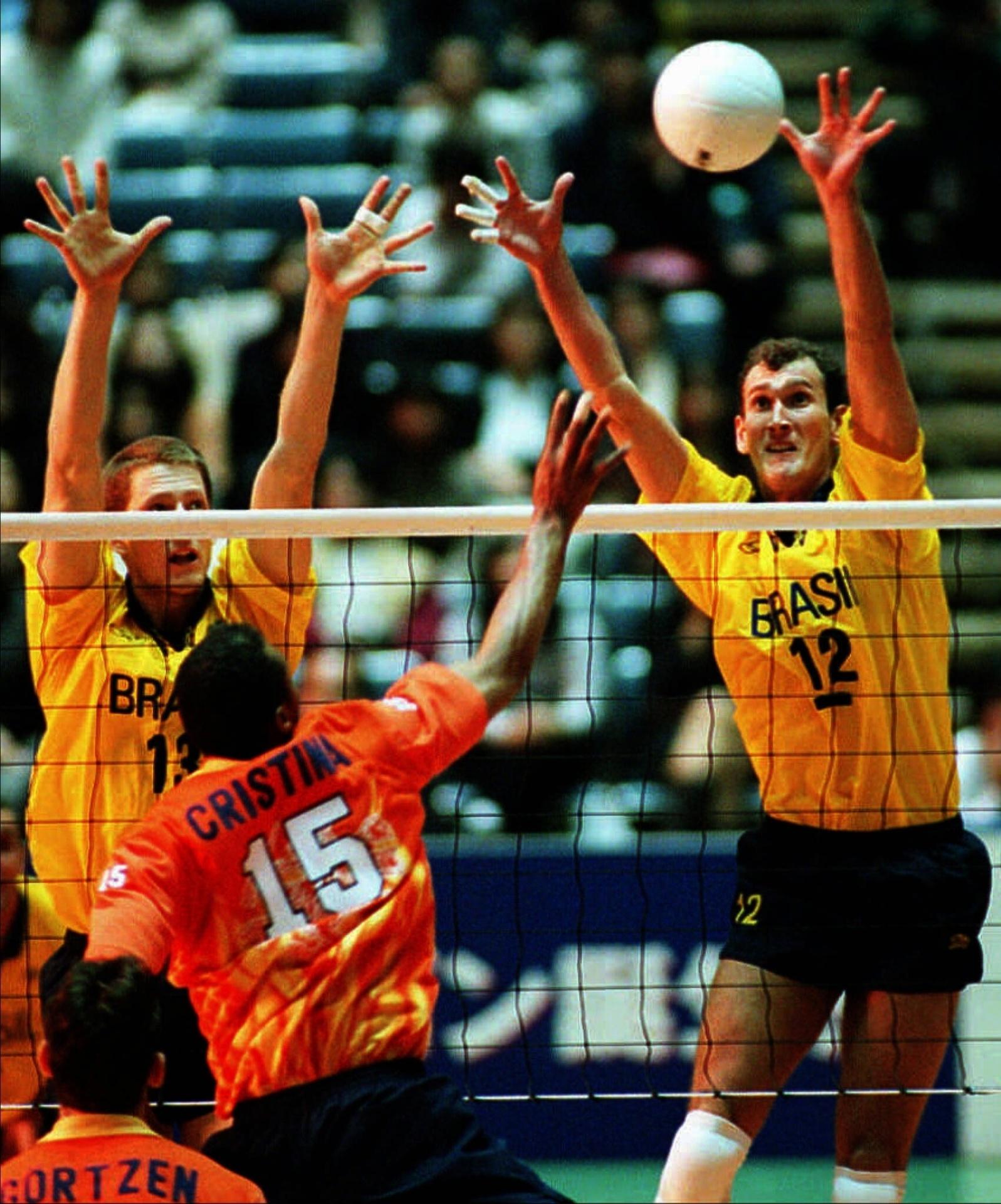 Gustavo e Nalbert (dir.) bloqueiam o atacante Albert Cristina, da Holanda, na vitória brasileira por 3x2, em novembro de 1997, ano de sua estreia na seleção.