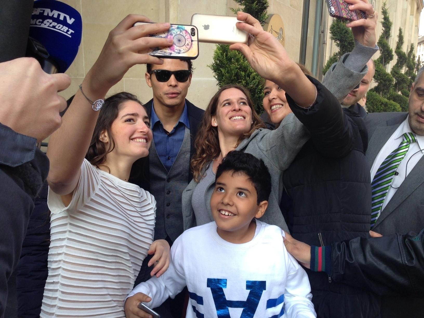 Thiago Silva posa para foto com torcedores na entrada de hotel em Paris