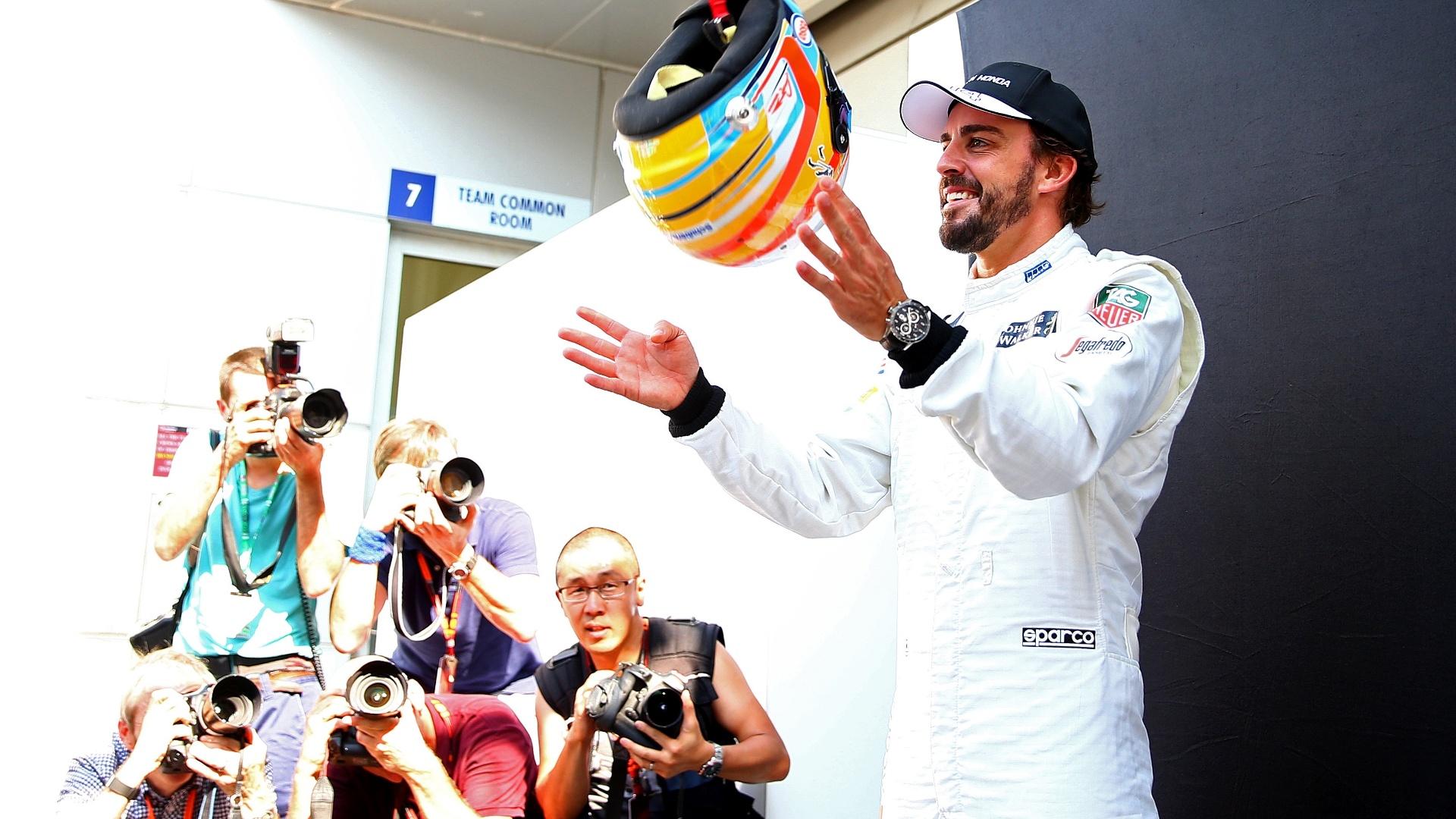 26.mar.2015 - Fernando Alonso brinca com seu capacete nos bastidores do circuito de Sepang, na Malásia