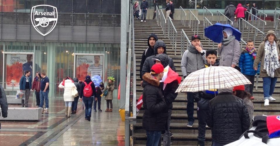 29.mar.2015 - Torcedores tentam 'driblar' a chuva em Londres horas antes do amistoso entre Brasil e Chile no Emirates Stadium