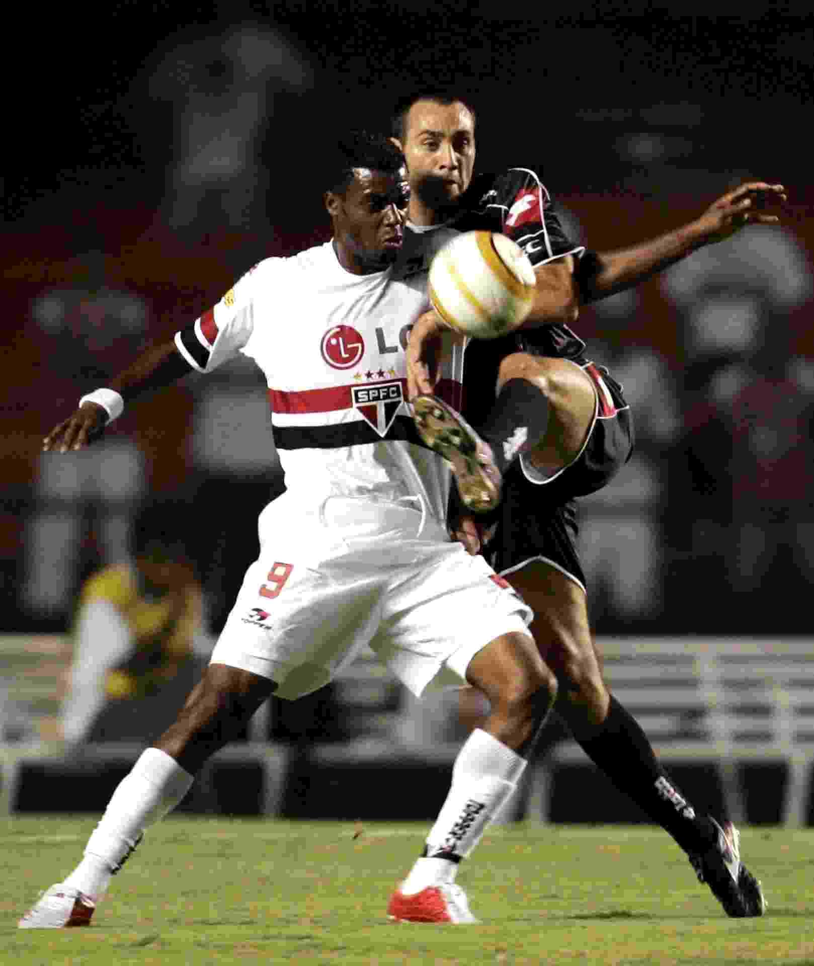 Grafite e Desábato disputam a bola no jogo São Paulo e Quilmes, válido pela fase de grupos da Libertadores 2005 - Reuters