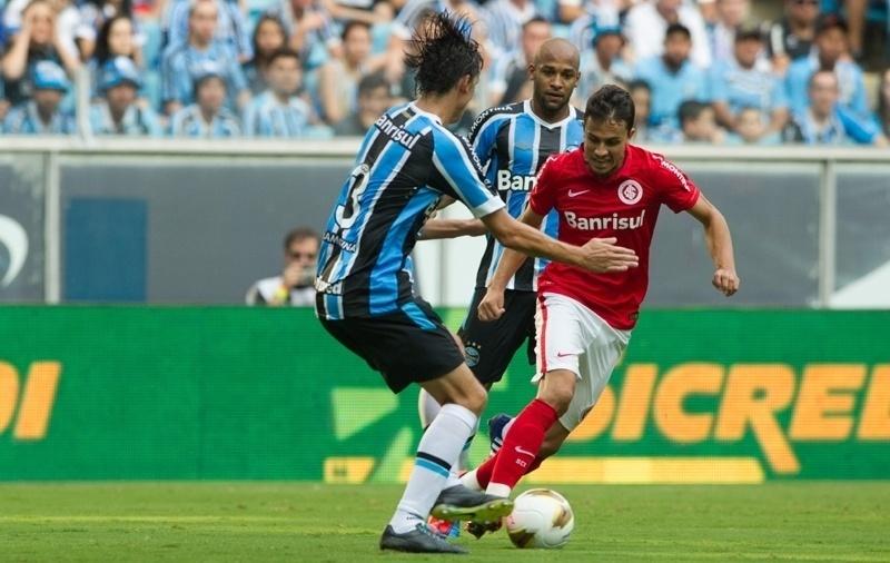 Nilmar, atacante do Inter, tenta o drible contra Geromel, zagueiro do Grêmio, no primeiro jogo da final do Campeonato Gaúcho