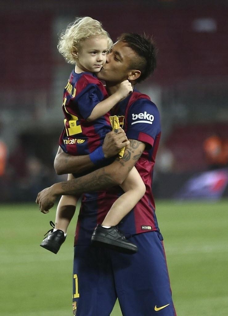 Neymar beija o filho no gramado do Camp Nou depois da vitória que garantiu o título da Copa do Rei