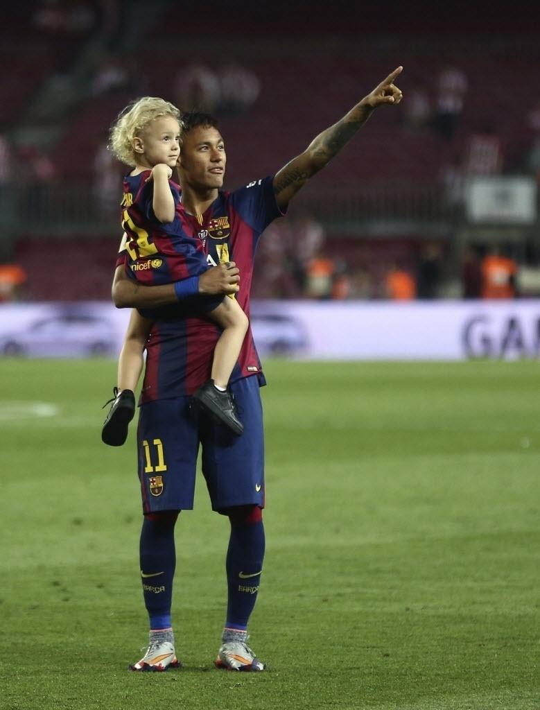 O atacante brasileiro aponta para alguém com o filho no colo