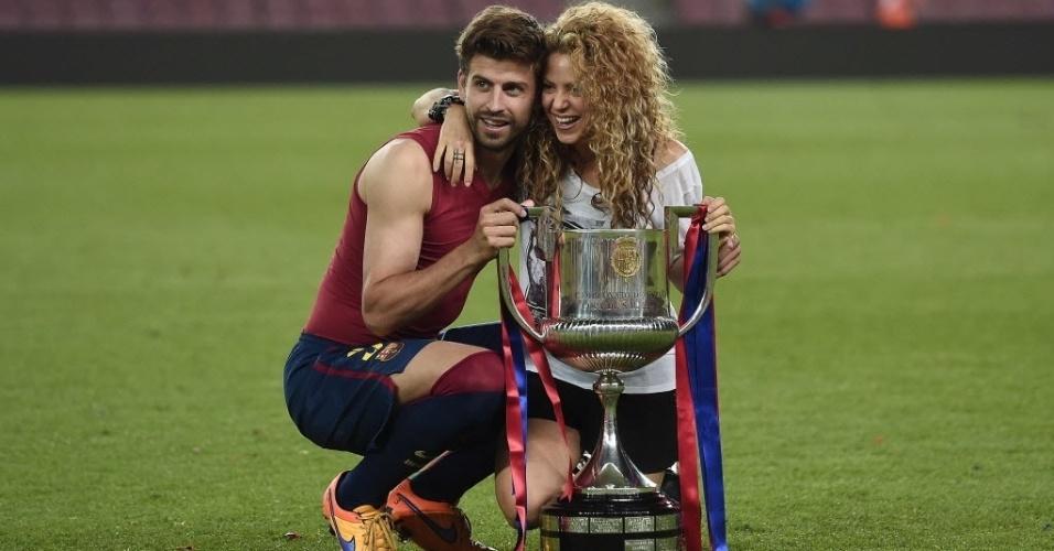 O zagueiro do Barcelona Piqué e a sua mulher, a cantora Shakira, seguram o troféu e comemoram o título da Copa do Rei