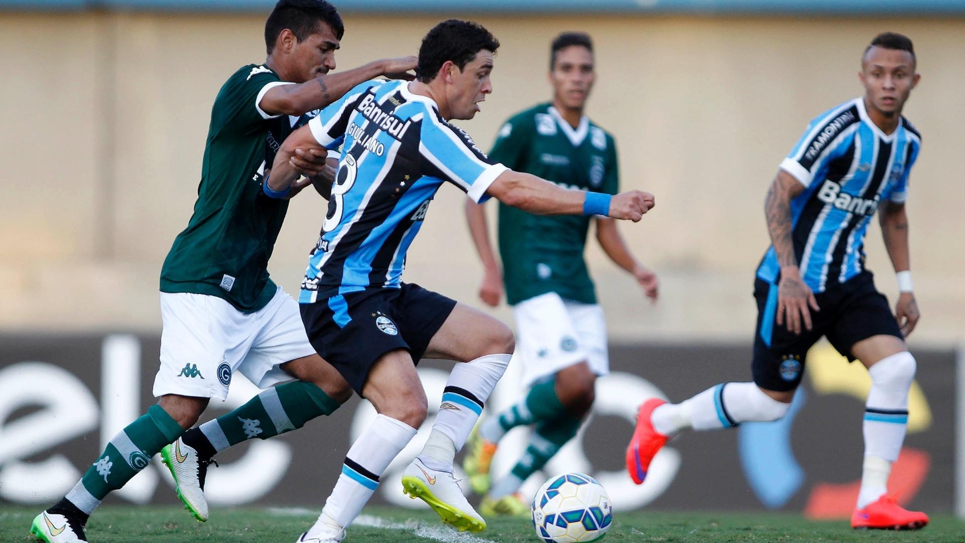 Giuliano, do Grêmio, tenta se livrar da marcação apertada do Goiás
