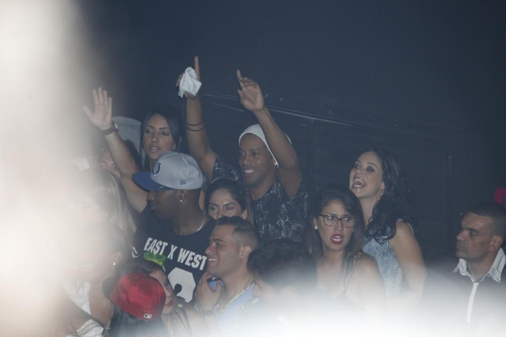 06.jun.2015 - Nos momentos em que não estava no palco, Ronaldinho estava sempre animado na pista e cercado por belas mulheres