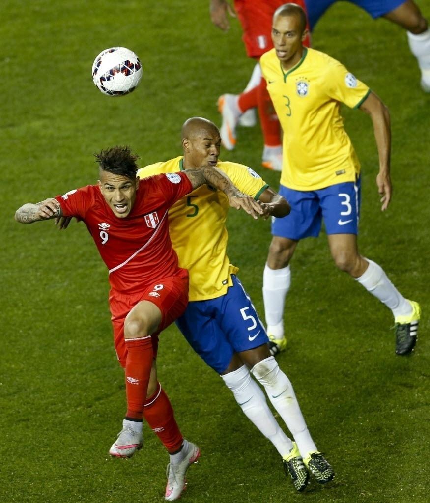 Paolo Guerrero sobe para disputar bola com Fernandinho