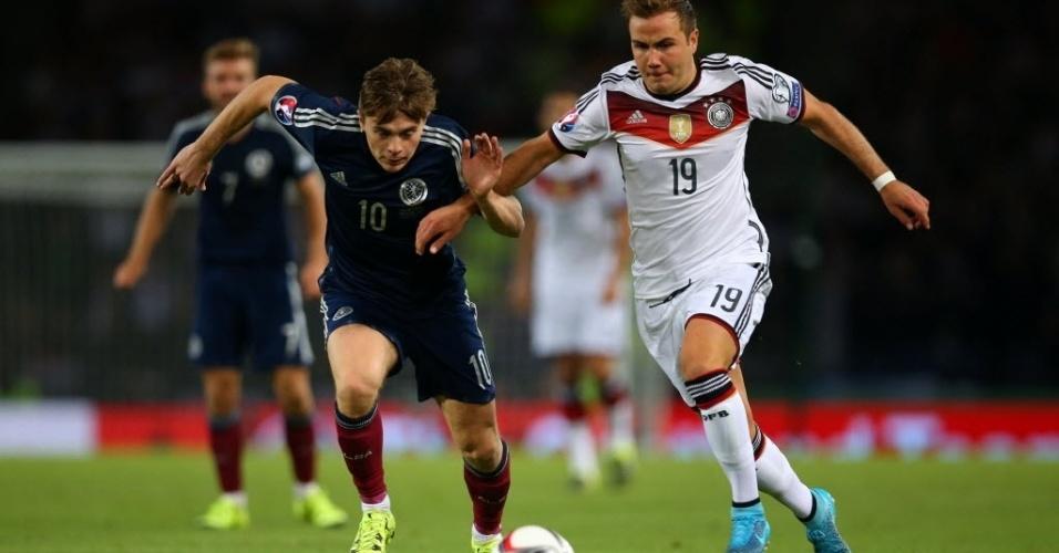 Mario Goetze, da Alemanha, disputa bola com James Forrest, da Escócia, pelas Eliminatórias da Eurocopa, nesta segunda-feira (7)