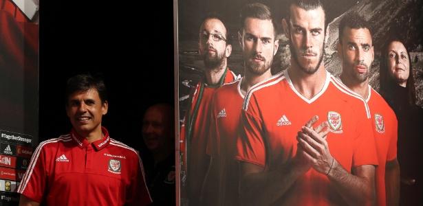 Chris Coleman, treinador do País de Gales, é fotografado ao lado de pôster da equipe