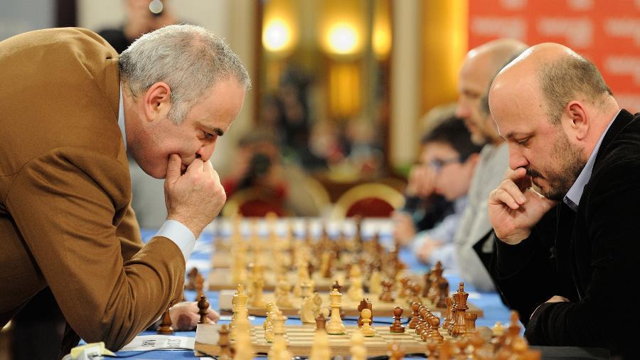 Garry Kasparov (esquerda) joga partida com 18 pessoas simultaneamente - Miso Lisanin/Xinhua
