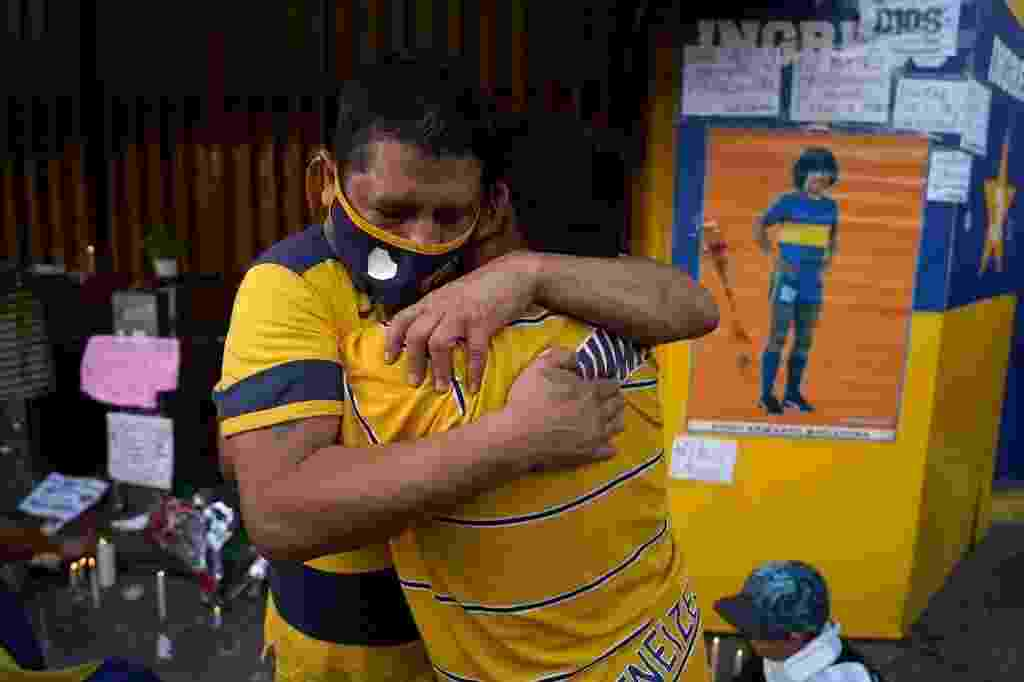 25.11.2020 - Torcedores se abraçam durante homenagem a Maradona em frente ao estádio La Bombonera - Ivan Pisarenko/AFP