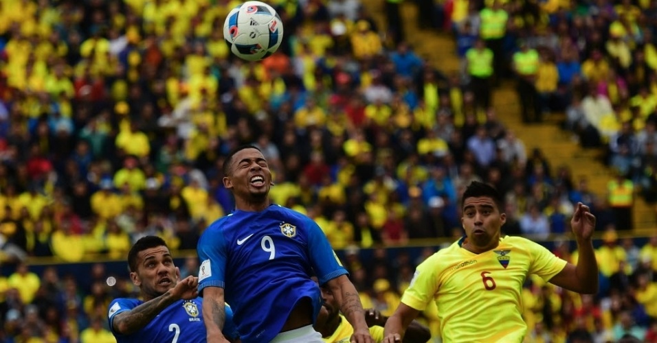 Gabriel Jesus e Daniel Alves sobem para tentar cabecear a bola na partida contra o Equador