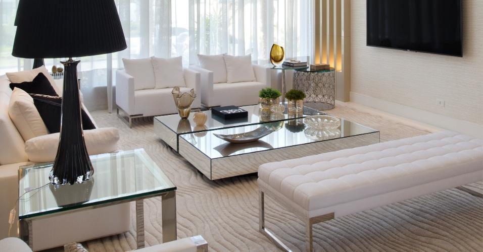 Sala de estar da casa de Alex Teixeira tem pé direito duplo, predominância por linhas retas e cores claras. Itens de decoração na cor preta como o abajour dão elegância ao ambiente