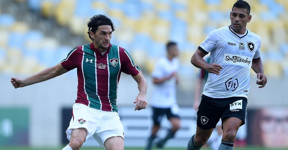 Matheus Ferraz carrega a bola pelo Fluminense e é seguido por Diego Souza, do Botafogo