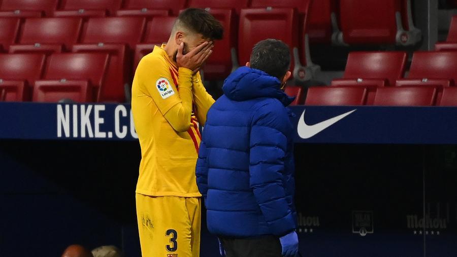 Piqué sofreu lesão no joelho contra o Atlético de Madri e deixou o campo chorando - GABRIEL BOUYS / AFP