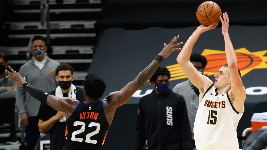 Nikola Jokic, do Denver Nuggets, arremessa sobre a marcação de Deandre Ayton, do Phoenix Suns, em jogo da NBA - Christian Petersen/Getty Images/AFP