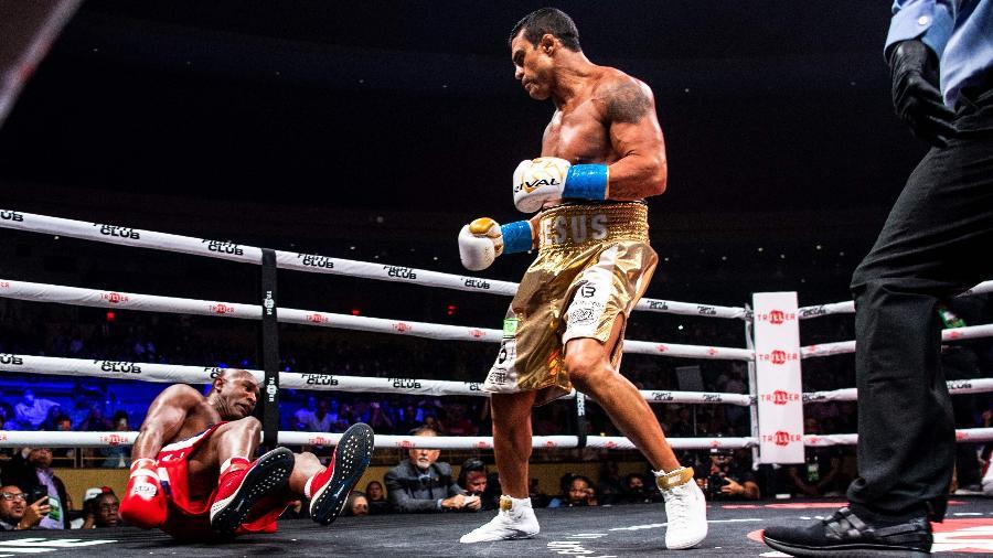 Vitor Belfort olha Evander Holyfield no chão durante luta de boxe nos Estados Unidos - Chandan Khanna/AFP