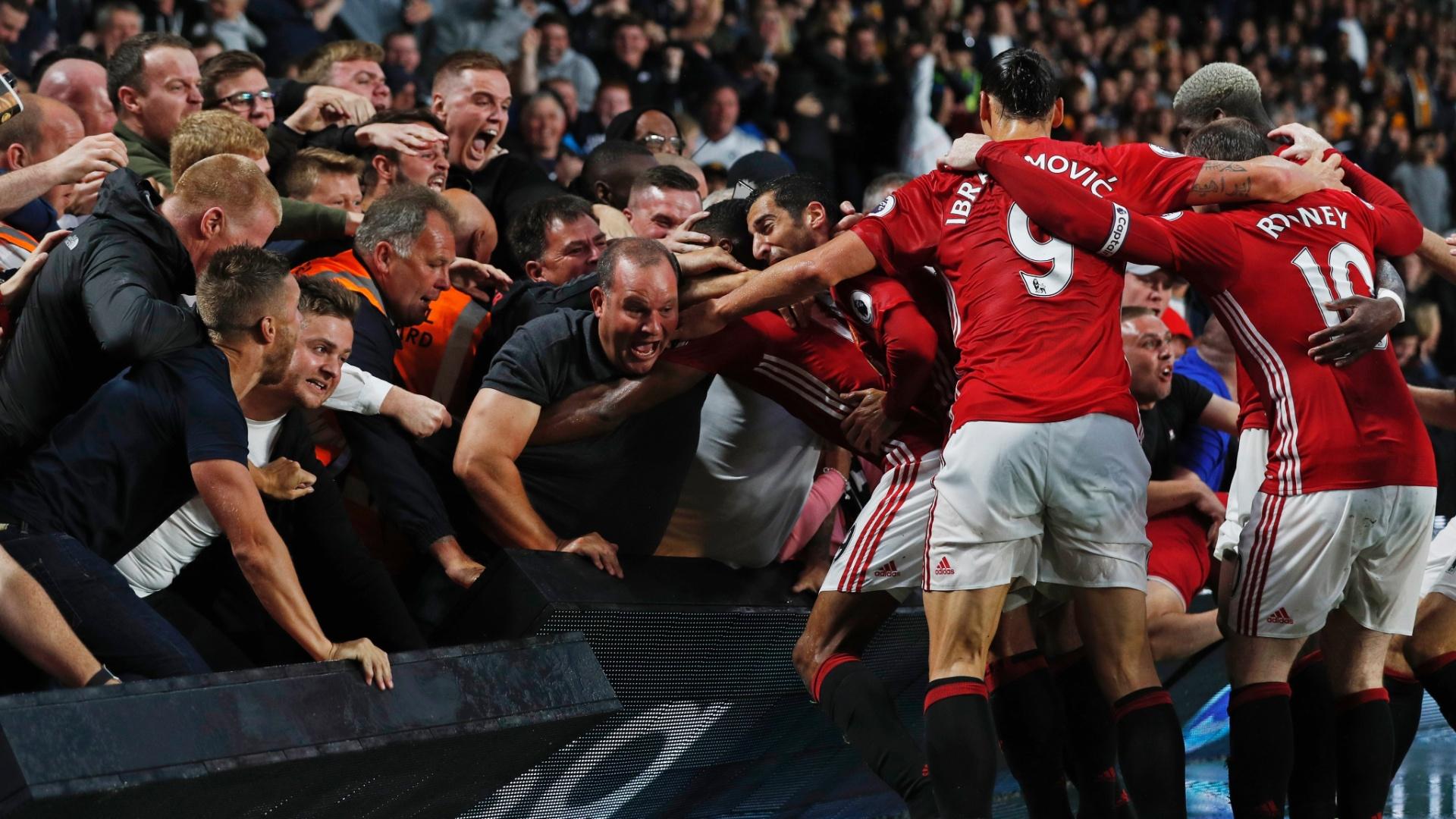 Torcedores e jogadores do Manchester United comemoram gol marcado no último minuto