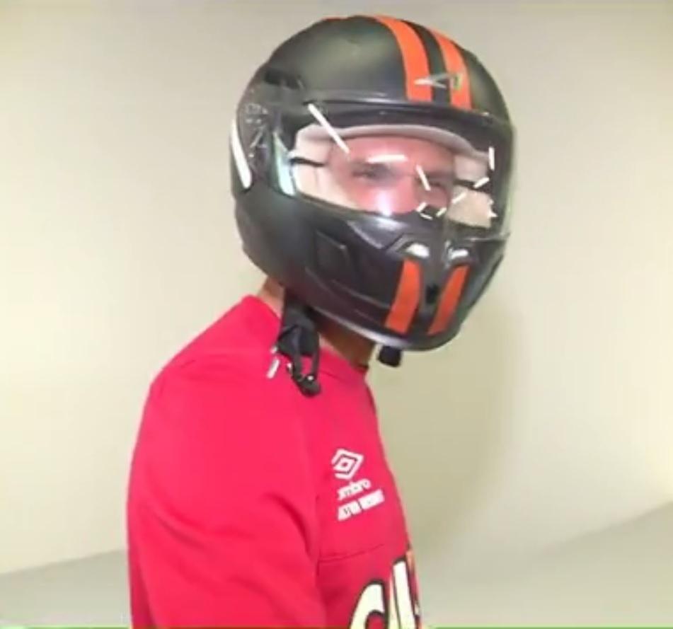 Milton Mendes chega ao CT do Atlético-PR com um capacete de motocicleta para esconder o novo penteado