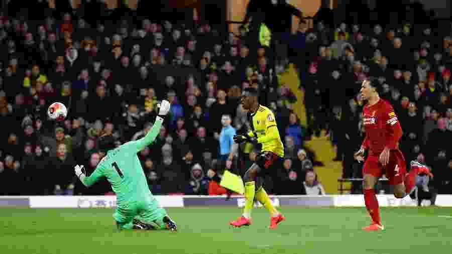 27.fev.2020 - Ismaila Sarr, do Watford, tira a bola do goleiro Alisson e marca seu 2º gol contra o Liverpool, observado pelo zagueiro Van Dijk. O time venceu por 3 a 0 derrubando a invencibilidade de 44 jogos dos Reds - David Klein/Reuters