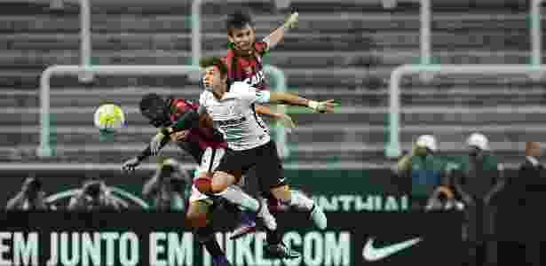 Romero, do Corinthians, disputa a bola entre Léo (dir.) e Paulo André (esq.), do Atlético-PR - Reinaldo Canato /UOL - Reinaldo Canato /UOL