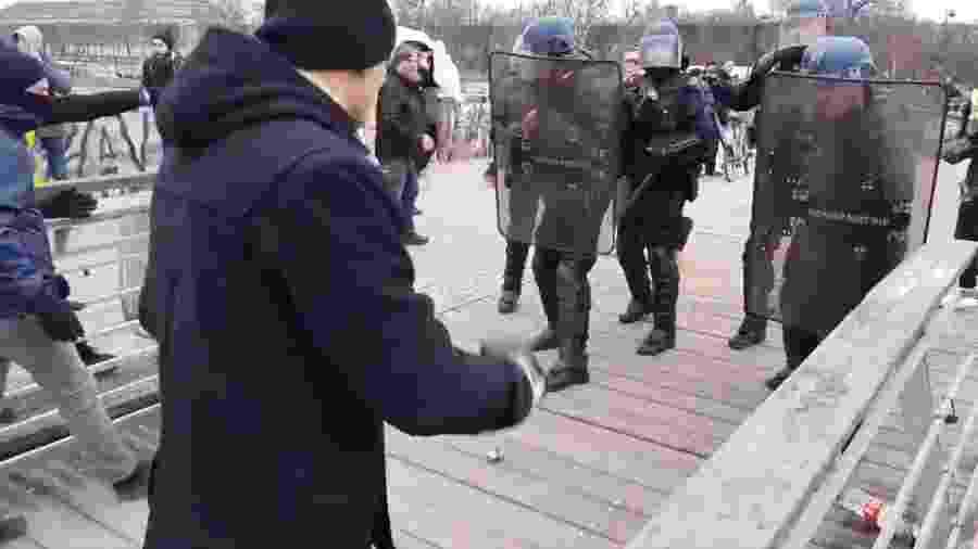 """Ao lado de """"coletes amarelos"""", pugilista profissional desferiu socos no capacete e no escudo de policial - Twitter/LinePress"""