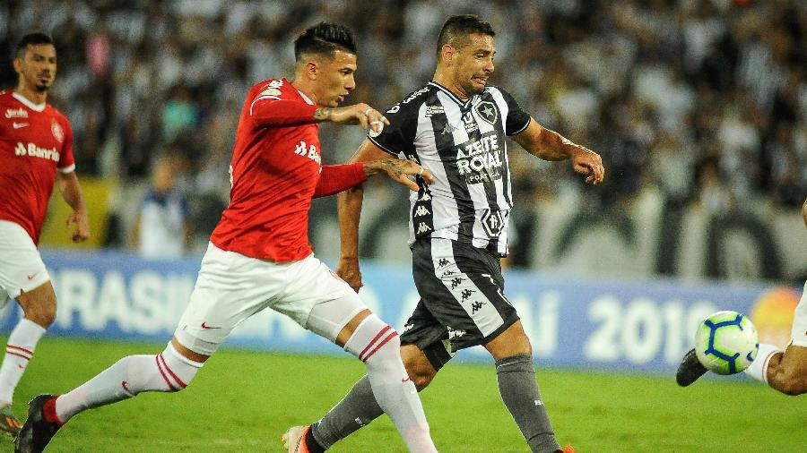Jogada entre Diego Souza e Victor Cuesta durante partida entre Botafogo e Internacional - Allan Carvalho/AGIF