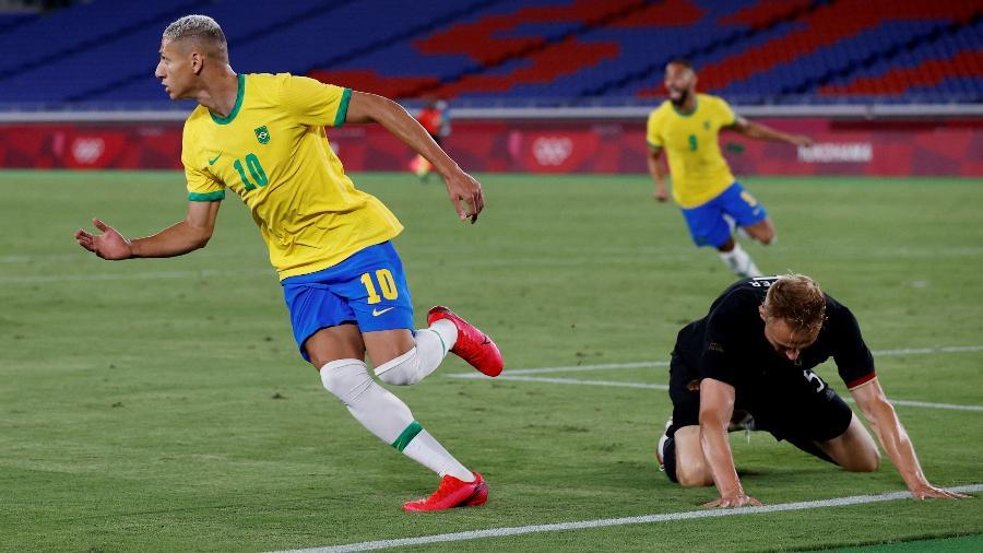 Richarlison sai para comemorar enquanto o zagueiro Pieper fica caído em um dos gols do Brasil contra a Alemanha - Phil Noble/Reuters