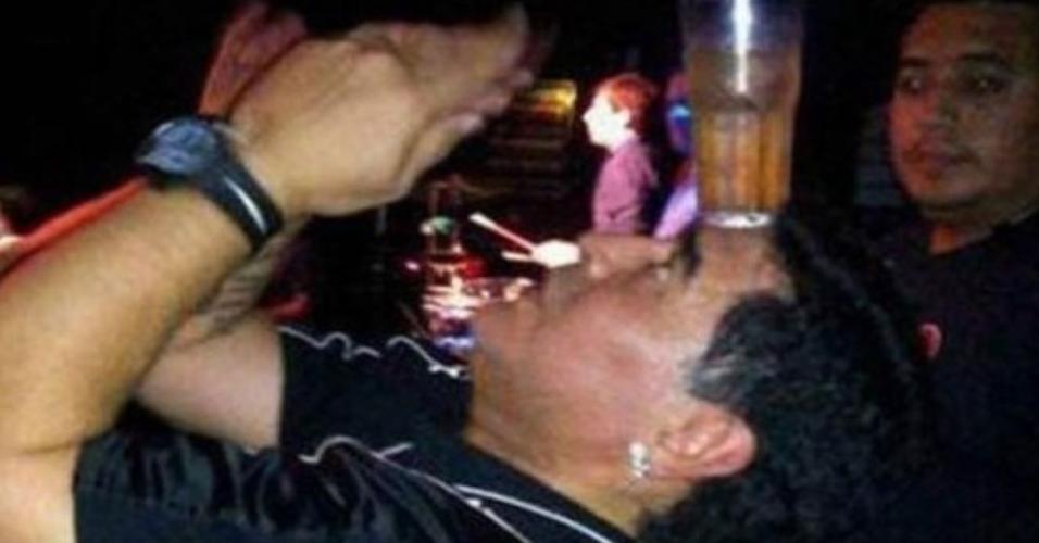 Maradona equilibra copo de bebida na testa