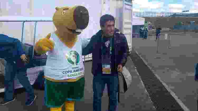 Jornalista tira foto com o mascote Zizito em Itaquera - José Edgar de Matos/UOL