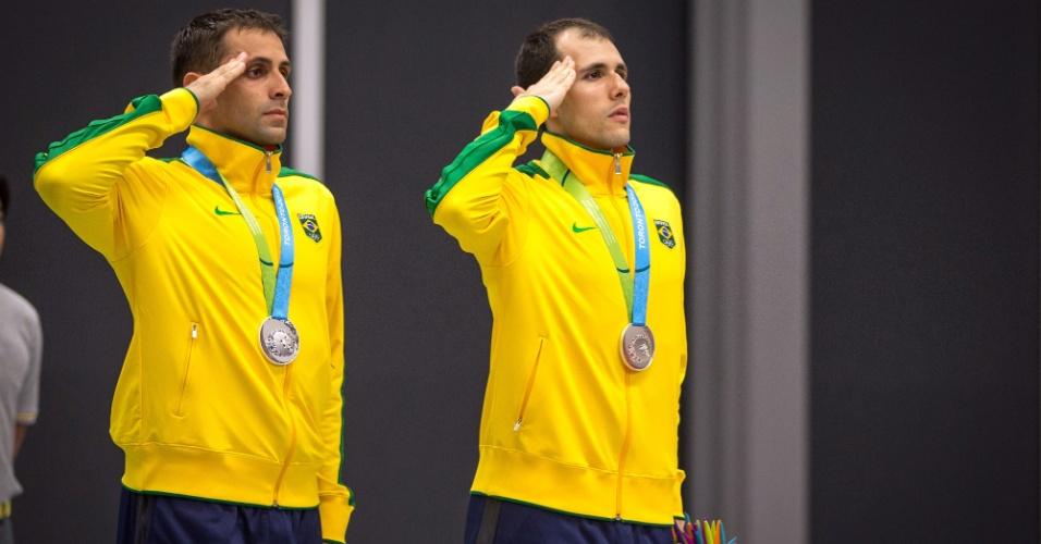 Atletas militares, Daniel Paiola e Hugo Arthuso prestam continência na hora do hino nacional. Brasileiros ganharam a medalha de prata