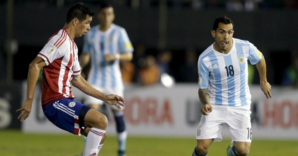 Tevez tenta superar a marcação de Cáceres no confronto entre Argentina e Paraguai pelas Eliminatórias da Copa