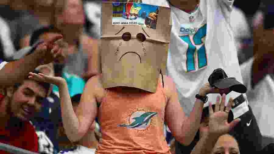Torcedora do Miami Dolphins usa saco de papel na cabeça para brincar com situação do time durante derrota para o Dallas Cowboys - Matthew Emmons/USA TODAY Sports