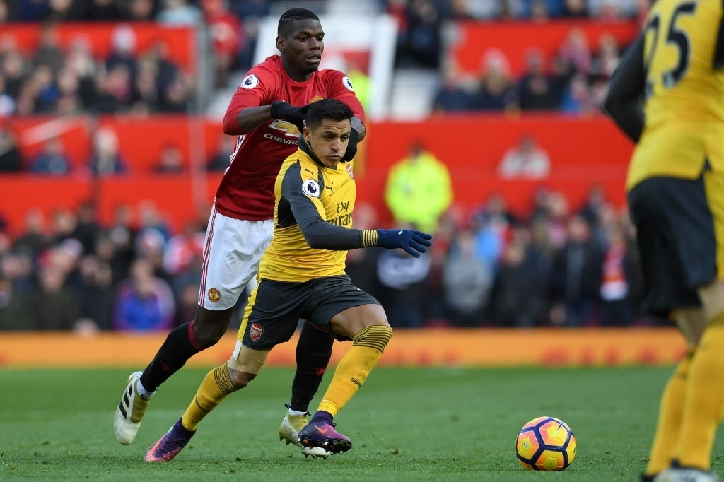 Paul Pogba e Alexis Sanchez disputam bola no clássico United x Arsenal